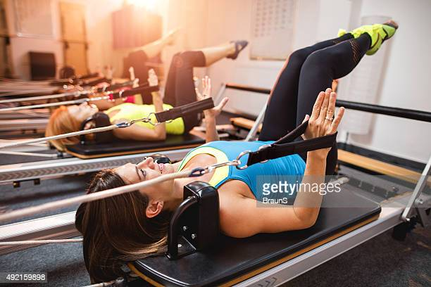 Pilates exercises on machines in a health club.