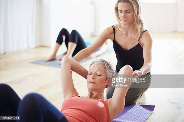 Pilates teacher holding student arms in class