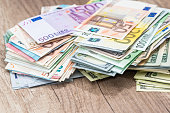 Pile money: dollars and euros banknotes on desk