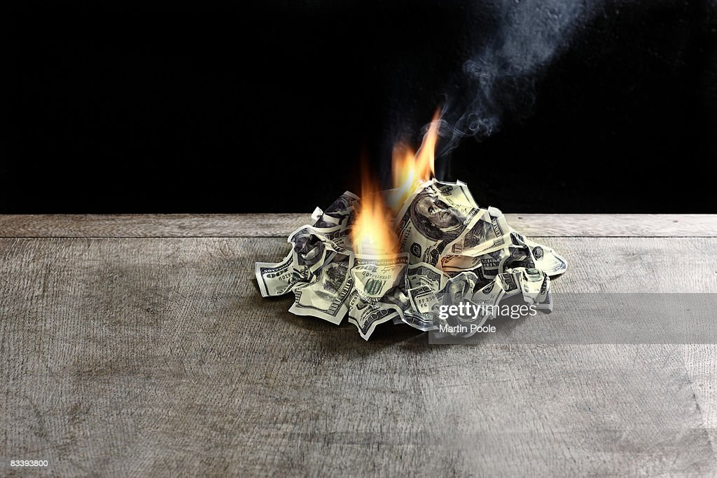 pile of 100 dollar notes on table on fire : Stock Photo
