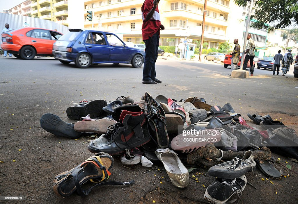A pile of abandoned shoes is picutred on January 2, 2013 in the street of Abidjian where at least 60 persons died in a stampede among crowds gathered for celebratory New Year's Eve fireworks that also left dozens injured. Ivory Coast began today three days of national mourning. AFP PHOTO / ISSOUF SANOGO