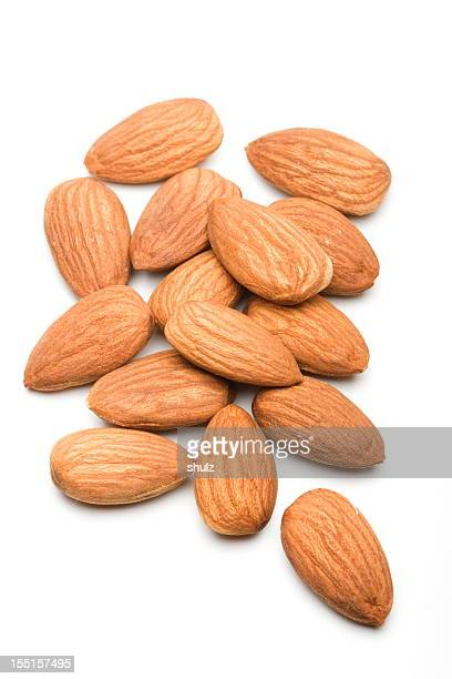 Pile of almonds on the table of a white background