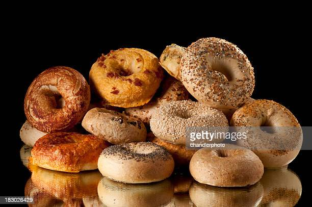 Pile of assorted bagels on reflective surface