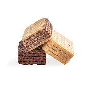pile of assorted square wafer biscuits isolated on white backdrop. closeup view