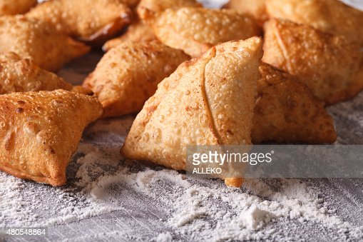 pile of baking samosas on a floured table. Horizontal : Stock Photo