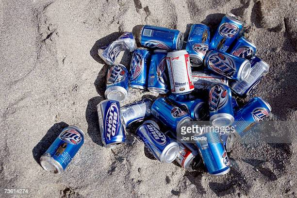 A pile of beer cans lays in the sand sun during spring break on South Beach March 16 2007 in Miami Beach Florida Students from universities and...