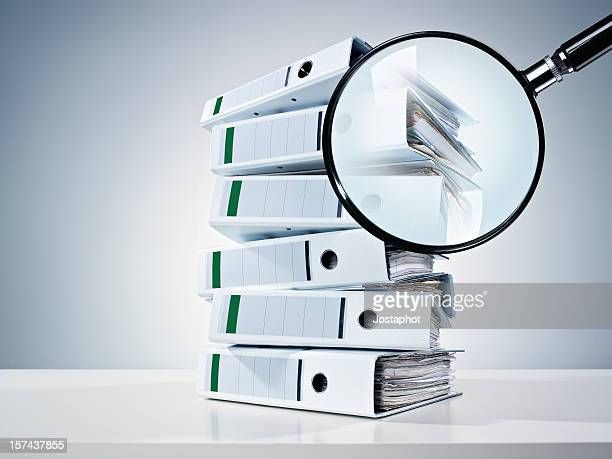 Pile of binders partially obscured by a magnifying glass