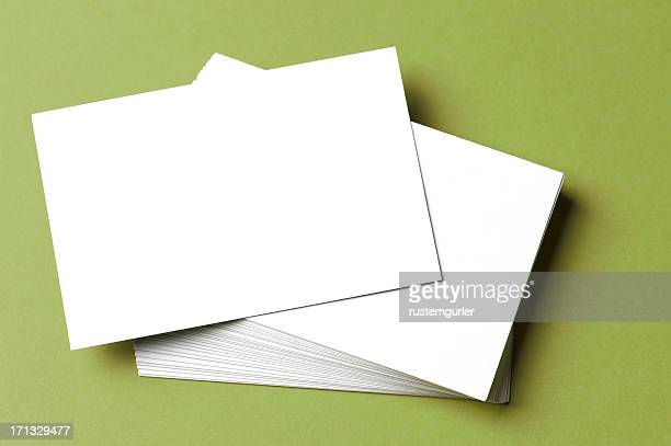 Pile of blank white cards on a green surface/background