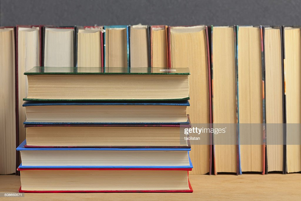 Pile of books on a wooden surface. : Stock Photo