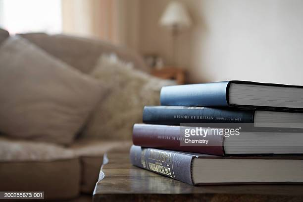 Pile of books on table in living room (focus on books and table)