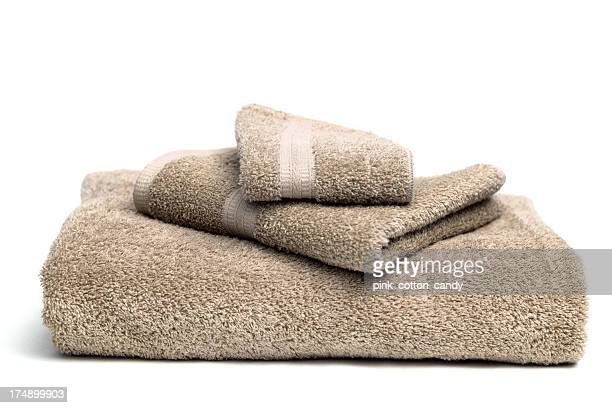 A pile of brown bath towels on a white background