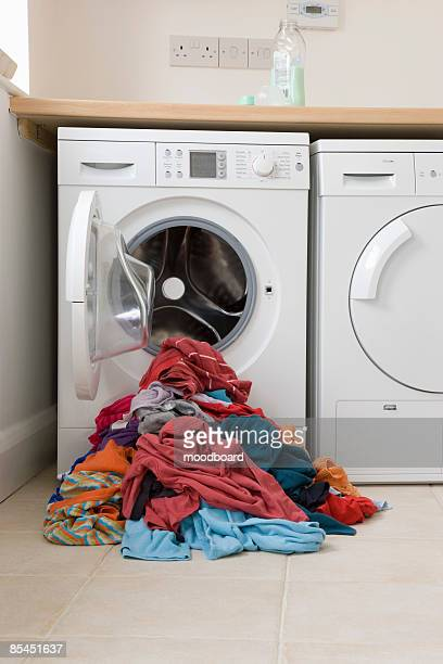 Pile of clothes in front of washing machine