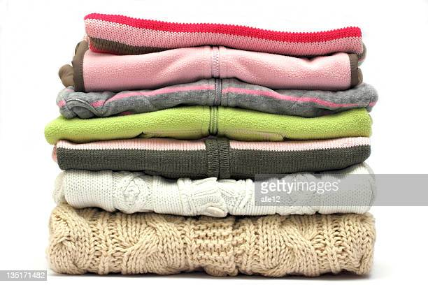 Pile of colored sweaters isolated on white