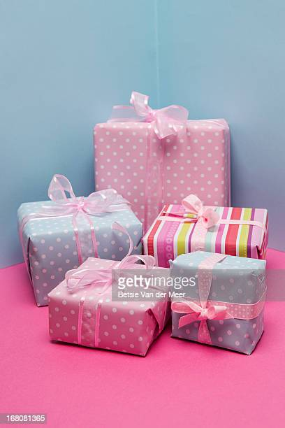 Pile of colorful presents with pink ribbons.