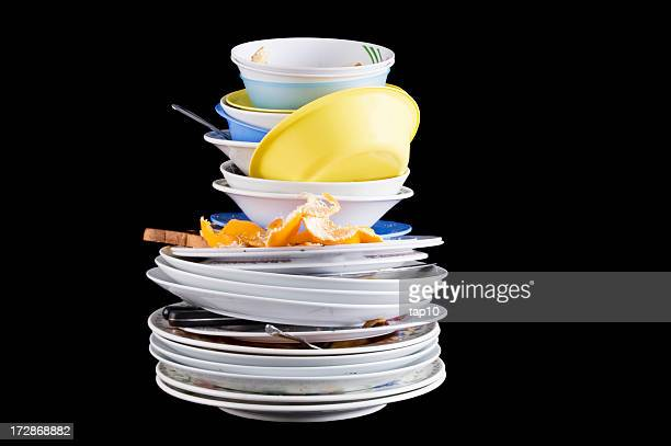 Pile of dirty dishes with an orange rind and rotting food