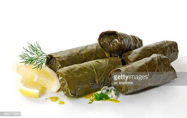 A pile of dolmades with lemon on a white background