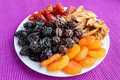A pile of dried fruits (apples, prunes, apricots, pears, cranberries) on a white plate on a purple background. Antioxidant mix. A useful product. Proper nutrition. Harvest.