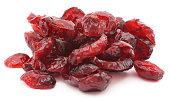Pile of dried shriveled red cranberries on white background