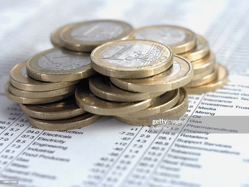 Pile of euro coins on list of share prices : Stock Photo