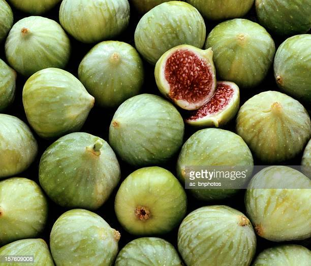 Pile of fresh green figs, one cut open