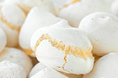 Pile of freshly backed homemade meringue cookies at farmers market. Artisan local pastry. Creamy texture pastel colors. French dessert confectionery. Food poster
