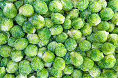 A pile of frozen Brussels sprouts in supermarket as background