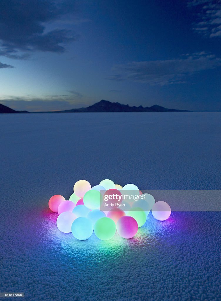 Pile of glowing orbs in desert at dusk. : Stock Photo
