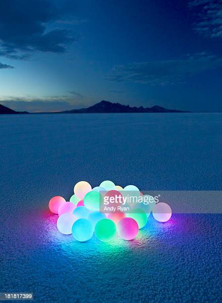 Pile of glowing orbs in desert at dusk.