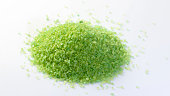 Pile of green himalayan salt on white background close up