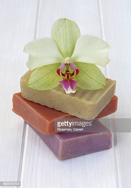 Pile of handmade soaps and orchid on white.