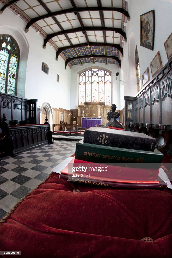 A pile of hymn and service books on a bench in a church; staindrop durham england