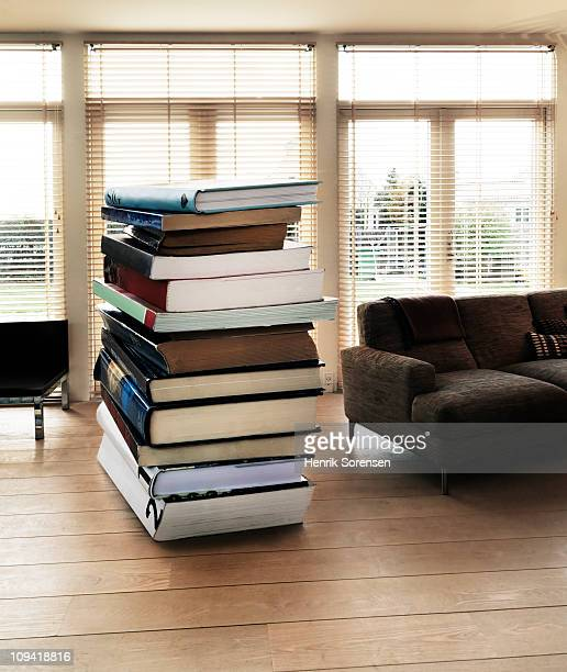 Pile of large scale books on floor in living room