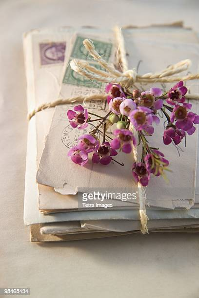 A pile of letter tied with twine and decorated with flowers