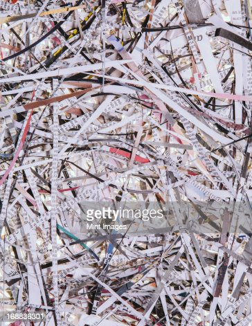 A pile of long thin shredded pieces of printed newspapers.