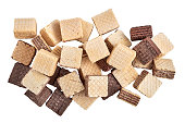A pile of mixed assorted square wafer biscuits isolated on white background. View from above