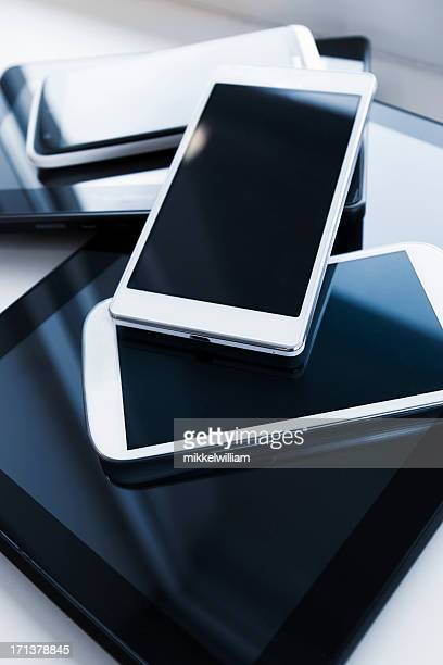 A pile of mobile phones and digital tablets