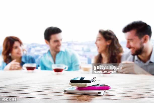 Pile de téléphones mobiles avec des amis s'amusant à l'arrière-plan