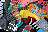 Many colorful socks form a textural background. Socks of different types and sizes.