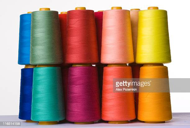 A pile of multicolored spools of sewing thread