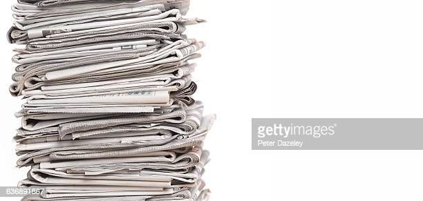 Pile of newspapers on white with copy space