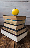 pile of old books and apple on wooden background
