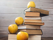 pile of old books and apples on wooden background