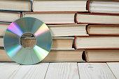 Pile of old books stacked on top of each other with a compact disc, the concept of audiobooks