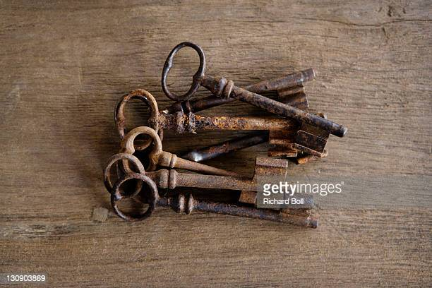 A pile of old rusty keys on a wooden table.