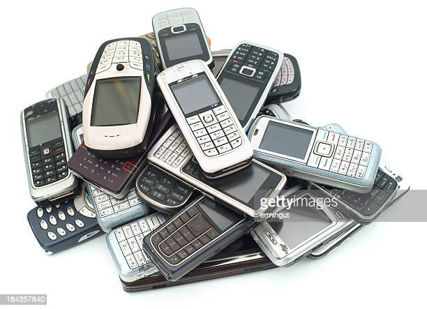 A pile of old used cellphones on a white background