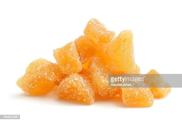 A pile of orange crystallized ginger on a white background