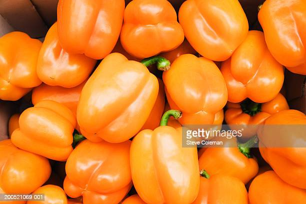 Pile of orange peppers on market stall, close-up