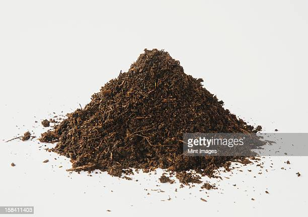 A pile of organic compost on a white background.