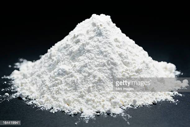 Pile of organic unbleached white flour, black backdrop