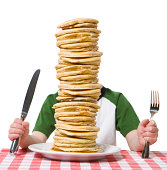 """Little boy hidden behind  a giant plate of pancakes, with a knife and fork visible on a table cloth. Please see my other photo with a similar theme, """"Pile of Sandwiches""""."""